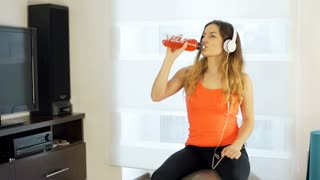 Girl listening music and drinking energy liquid while smiling to the camera, ste