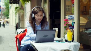 Girl listening music and drinking latte while using laptop in the cafe