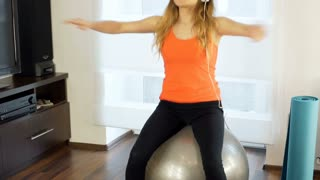 Girl listening music and exercising on the ball in her joga, steadycam shot