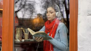 Girl listening music and reading book by the cafe's window, steadycam shot