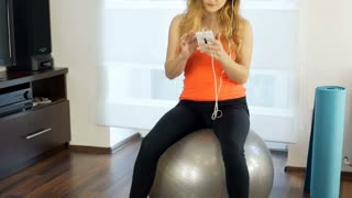 Girl listening music and using smartphone while sitting on the exercising ball,