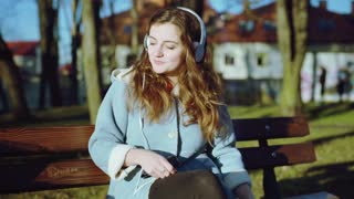 Girl listening music in the park while sitting on the bench