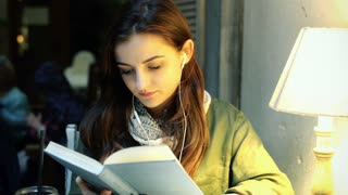 Girl listening music on earphones and reading book in the cafe
