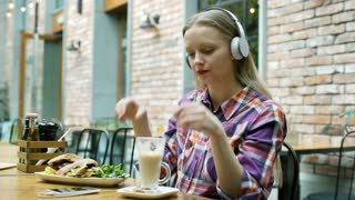 Girl listening music on headphones and drinking coffee in the cafe