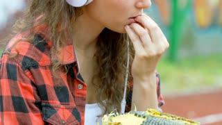 Girl listening music on headphones and eating sunflower's seeds