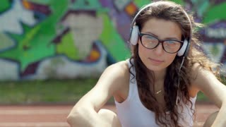 Girl listening music on headphones and looking to the camera, steadycam shot
