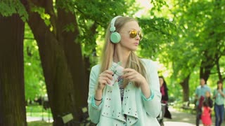 Girl listening music on headphones and moving her body while standing on pathway