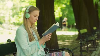 Girl listening music on headphones and reading book in the park