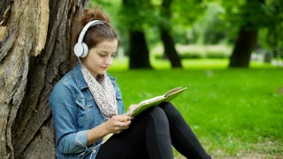 Girl listening music on headphones and writing in notebook in the park