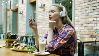 Girl listening music on headphones in the cafe and smiling to the camera