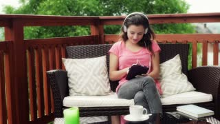Girl listening music on tablet and smiling to the camera on patio