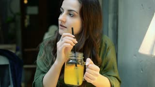 Girl looking around the cafe and drinking orange juice