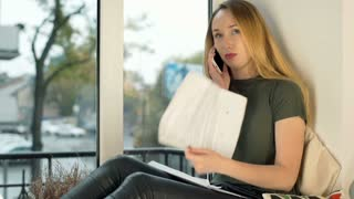 Girl looking worried while talking on cellphone about her bills