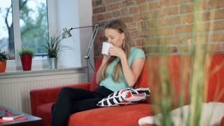 Girl looks calm while talking on cellphone and drinking tea in the living room