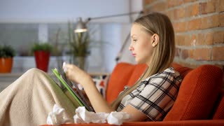 Girl looks unwell while sitting under blanket on the sofa and working on papers