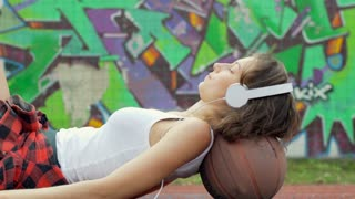 Girl lying on the ball and listening music while having a nap