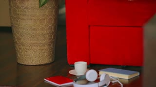 Girl lying on the red sofa and texting on smartphone, steadycam shot