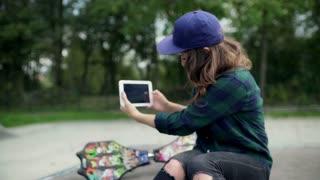 Girl making film on tablet while spending time in skate park