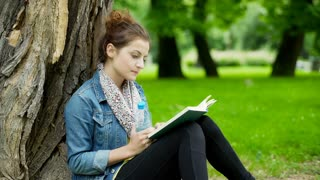 Girl reading book and drinking water while sitting in the park