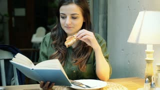 Girl reading book in the cafe and eating pizza at night