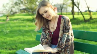Girl reading book in the park and smiling to the camera