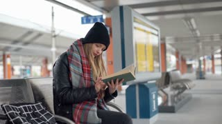 Girl reading book on a platform and smiling to the camera
