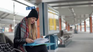 Girl reading her notes on a platform and smiling to the camera