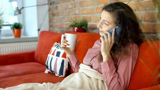 Girl relaxing under blanket while chatting on cellphone