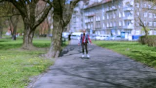 Girl riding on rollerblades in the park and smiling to the camera
