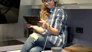 Girl sits on worktop in the kitchen and watches video on tablet, steadycam shot