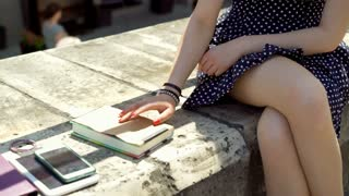 Girl sitting and tapping on the book cover and wearing vintage dress