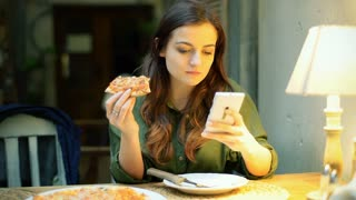 Girl sitting at night in the cafe and browsing internet while eating pizza