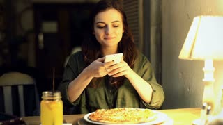 Girl sitting at night in the cafe and doing photo of pizza