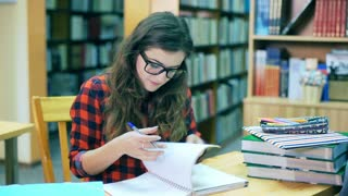 Girl sitting at the table in the library and writing something in notebook