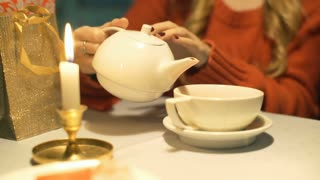 Girl sitting by the table and pours tea to the cup at christmas evening