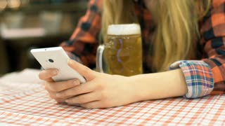 Girl sitting by the table with a beer and using smartphone, steadycam shot