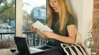 Girl sitting by the window and looking on her bills, steadycam shot