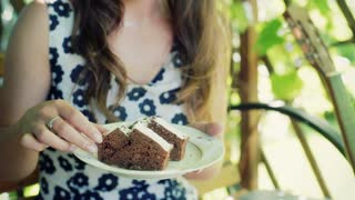 Girl sitting in the arbor and eating slice of cake