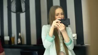 Girl sitting in the cafe and doing photo in the mirror