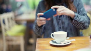 Girl sitting in the cafe and doing photo of cup on smartphone