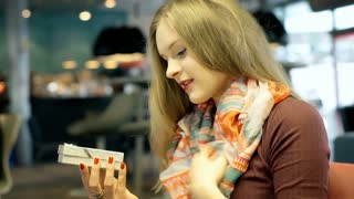 Girl sitting in the cafe and opens present with necklace inside it