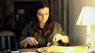 Girl sitting in the cafe at night and cutting pizza