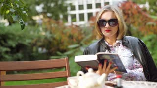 Girl sitting in the outdoor cafe and reading book