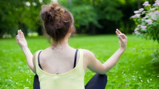 Girl sitting in the park and doing yoga, steadycam shot