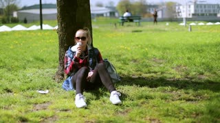 Girl sitting in the park and eating ice cream