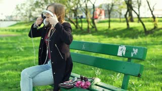 Girl sitting in the park and finish listening music on headphones