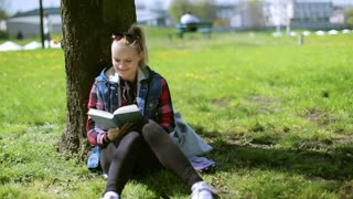 Girl sitting in the park and reading book