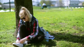 Girl sitting in the park and tying shoe laces