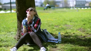 Girl sitting in the park and using bubble blower