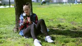 Girl sitting in the park and using smartphone